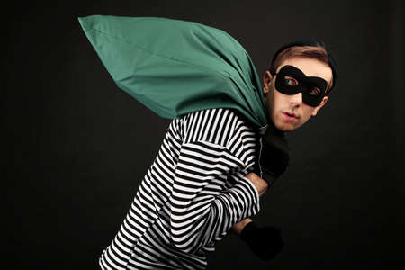 crook: Thief with bag isolated on black Stock Photo