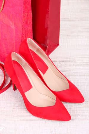 Beautiful red female shoes, belt and shop bags photo