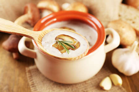 Mushroom soup in wooden spoon and pot, on wooden table, on sackcloth background photo