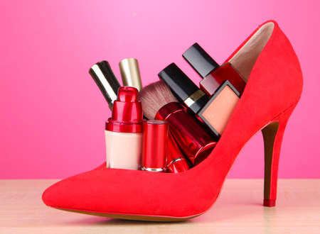 Beautiful red female shoe with cosmetics, on pink background photo
