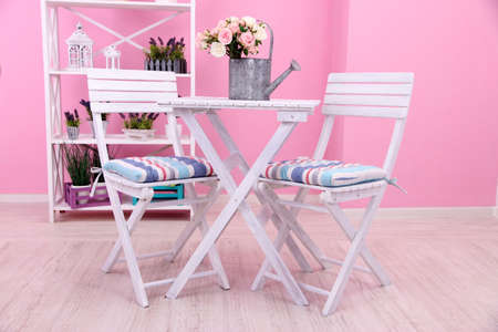 Garden chairs and table with flowers on shelves on pink background photo