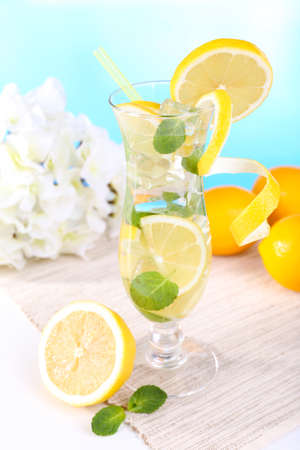 Glass of cocktail with lemon and mint on table on light blue background photo