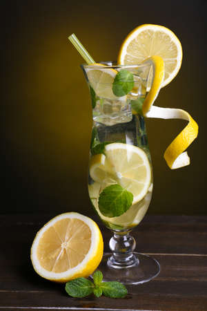 Glass of cocktail with lemon and mint on table on dark yellow background photo