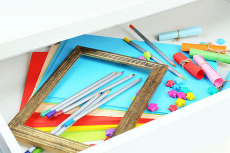 Colorful paper in open desk drawer close up  photo