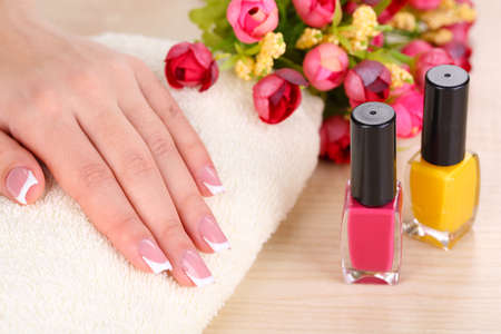 Beautiful woman hands with french manicure and flowers on wooden background photo