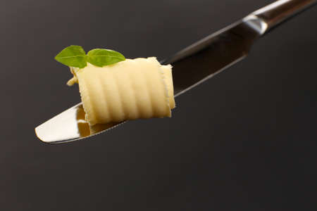 Curl of fresh butter with basil on knife on grey background