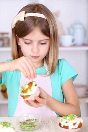 Klein meisje versieren van cupcakes in de keuken thuis Stockfoto