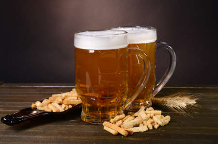 Glasses of beer with snack on table on dark background photo
