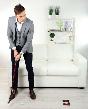 Elegant young businessman playing mini golf at home photo