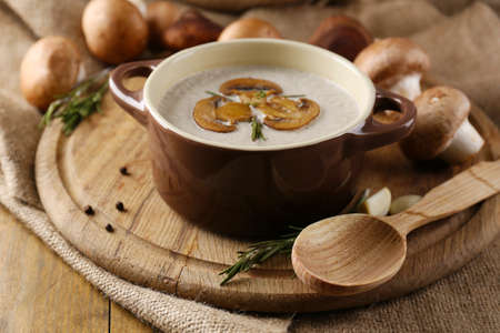 Composition with mushroom soup in pot, fresh and dried mushrooms, on wooden table, on sackcloth background Stock Photo - 25753546