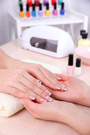 Young woman getting manicure in beauty salon photo