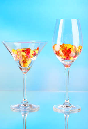 Goblets with pills on blue background photo