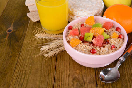 Delicious oatmeal with fruit in bowl on table close-up photo