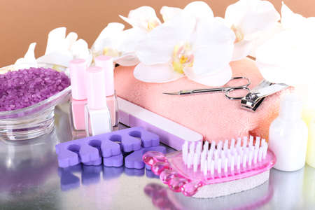 Pedicure set on table on beige background photo