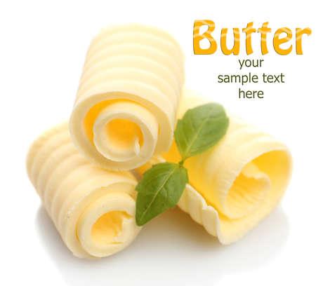 Krullen van verse boter met basilicum, geïsoleerd op wit