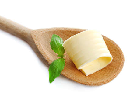 butterfat: Curl of fresh butter with basil on wooden spoon, isolated on white