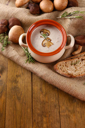 Mushroom soup in pot, on wooden background Stock Photo - 25871670