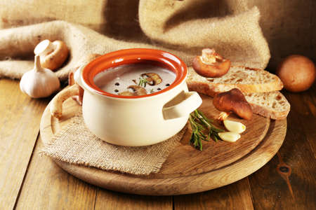 Mushroom soup in pot, on wooden table, on sackcloth background photo