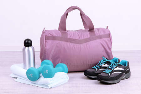Sports bag with sports equipment in gymnasium photo