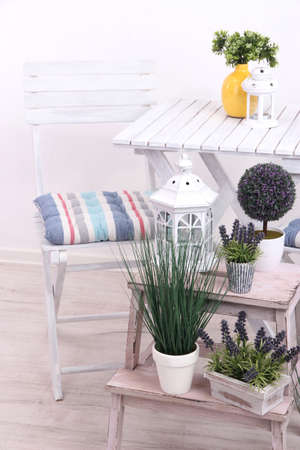 Garden chair and table with flowers on wooden stand on white background photo