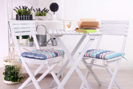 Garden chairs and table with flowers on shelves on white background photo
