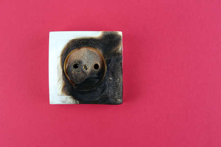 Burned plug socket close up photo