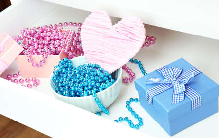 Gift boxes and beads in open desk drawer close up  photo