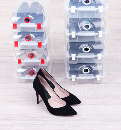 Shoes in plastic boxes and female shoes on floor in room Stock Photo - 25879653