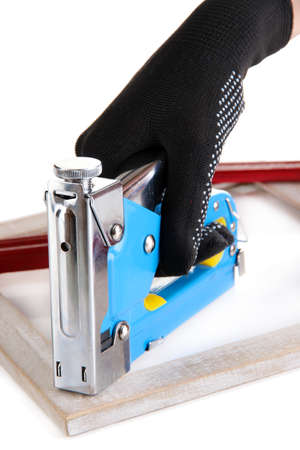 staple gun: Fastening wooden frame using construction stapler isolated on white