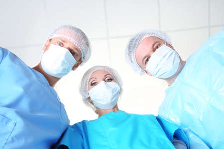 View from below of surgeons in protective work wear during operation photo