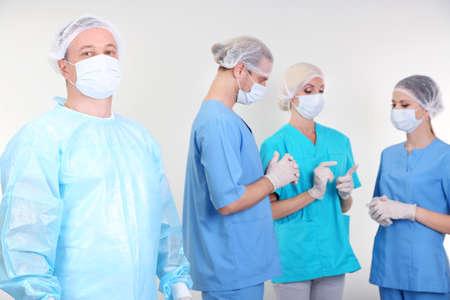 Surgeons standing on grey background photo