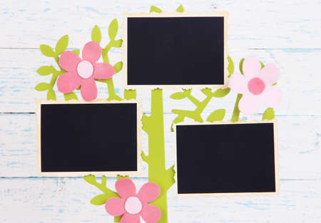 Holder in form of tree with instant photo cards on color wooden background photo