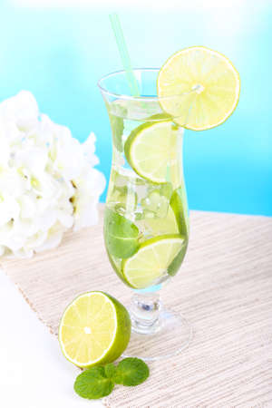 Glass of cocktail with lime and mint on table on light blue background photo