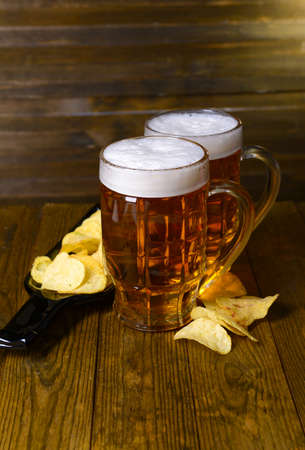 Glasses of beer with snack on table on wooden background photo