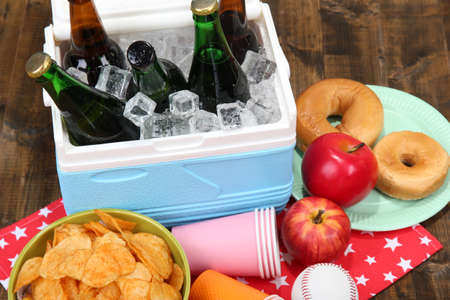 water cooler: Ice chest full of drinks in bottles on color napkin, on wooden background