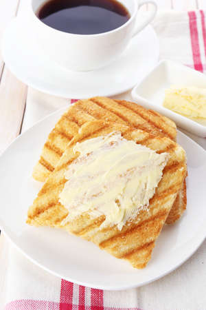 browned: Grilled bread with butter and cup of coffee on wooden table