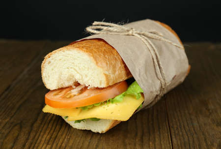Fresh and tasty sandwich on wooden table on black background photo