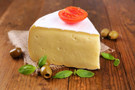 chees: Tasty Camembert cheese with tomato, basil and olives, on wooden table