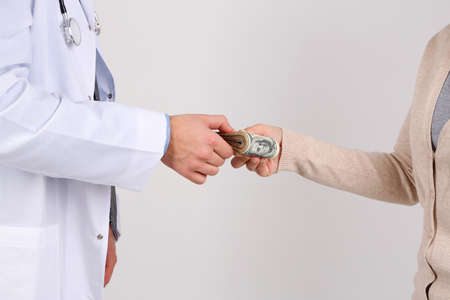 Male Doctor receiving money from patient, isolated on white photo