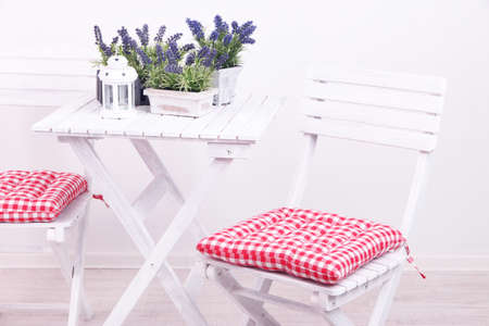 Garden chairs and table with flowers on white background photo