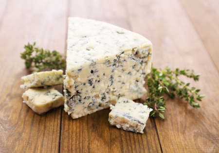 chees: Tasty blue cheese with thyme, on wooden table