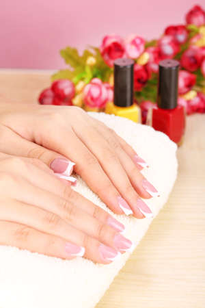 Beautiful woman hands with french manicure and flowers on table close up photo
