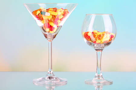 Goblets with pills on natural background photo