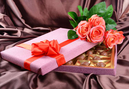 Delicious chocolates in box with flowers on brown background photo