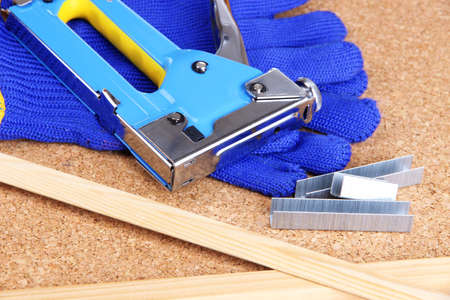 lath in modern: Construction stapler with gloves and staples on cork board close up Stock Photo
