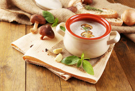 Mushroom soup in pot, on wooden background photo