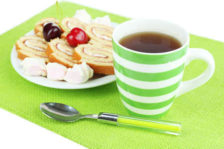 Cup of tea and sweets isolated on white photo