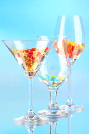 Goblets with pills on blue background