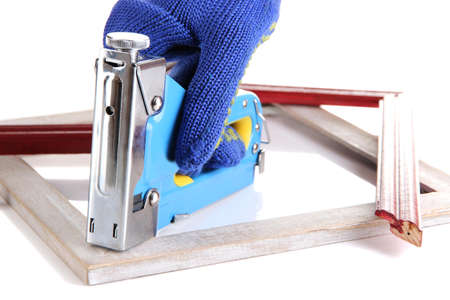 Fastening wooden frame using construction stapler isolated on white photo