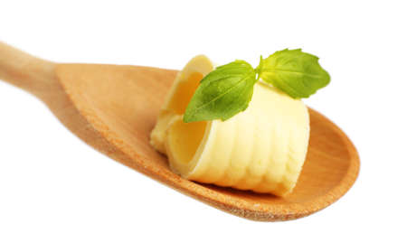 Curl of fresh butter with basil on wooden spoon, isolated on white photo